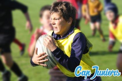 Un jeune joueur tient son ballon de rugby avec détermination
