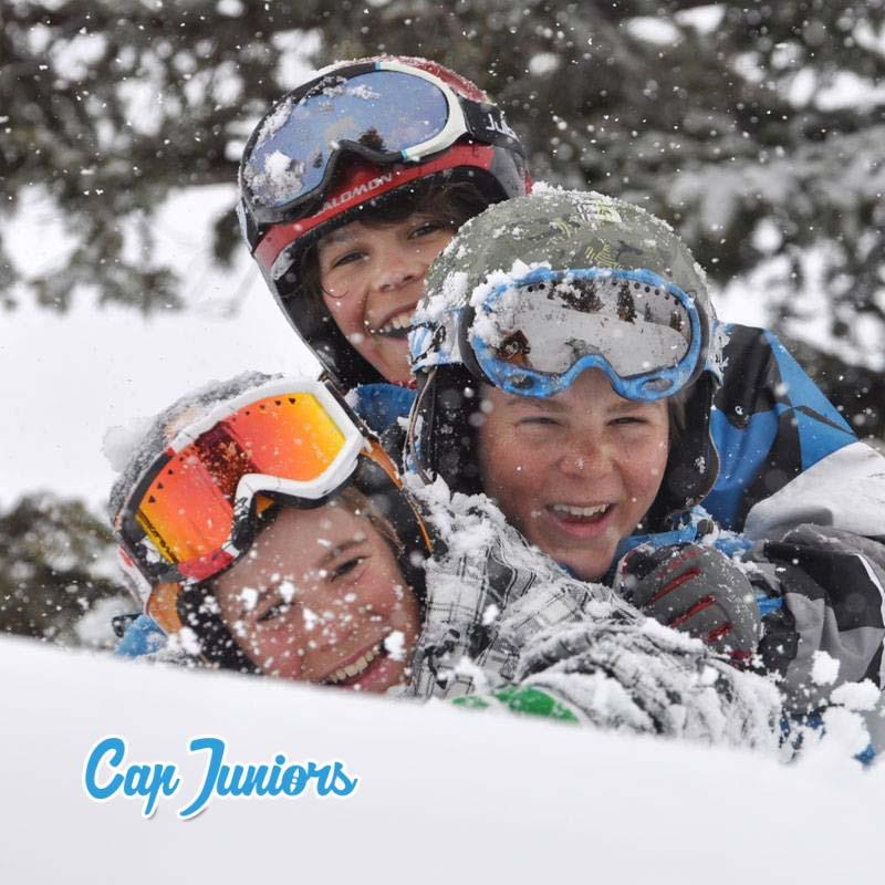 3 gamins jouent dans la poudreuse, casques et lunettes de ski bien en place