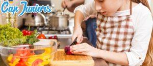 Une petite fille prépare un plat cuisiné en atelier cuisine, une colonie activité manuelle